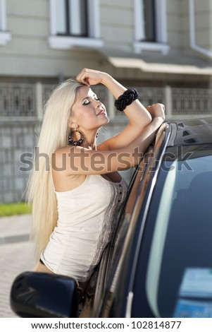 happy young woman with car - sexy rich lady driver with long blond healthy hair at automobile . spring - summer portrait . beautiful slim fashion girl posing near car