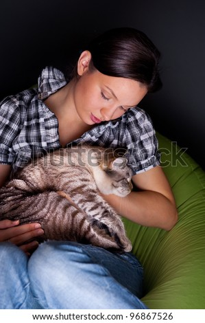 Happy young woman with cat, relaxed on the beanbag couch. - stock photo