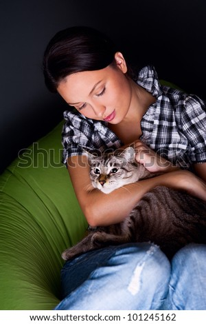 Happy young woman with cat, relaxed on the beanbag couch.g woman with cat, relaxed on the beanbag couch.