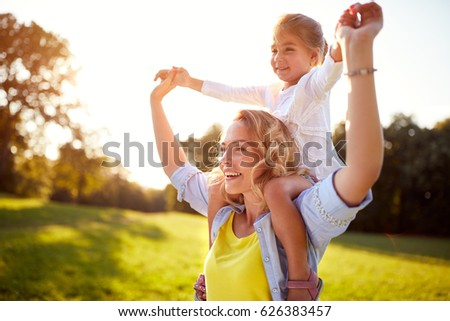 Happy young woman with child together outdoor