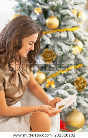 Happy young woman with christmas postcard sitting near christmas tree