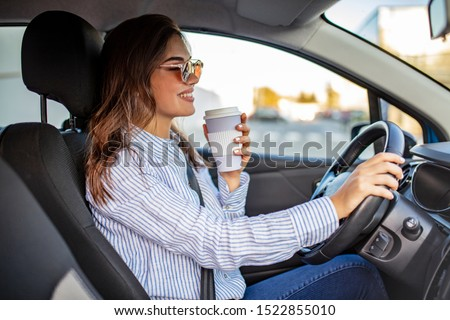 Happy young woman with coffee to go driving her car. Woman sipping a coffee while driving a car. Young woman drinking coffee while driving her car. Attractive brunette drives a car