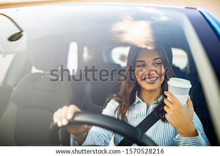 Happy young woman with coffee to go driving her car. Woman sipping a coffee while driving a car. Young woman drinking coffee while driving her car. Attractive brunette drives a ca