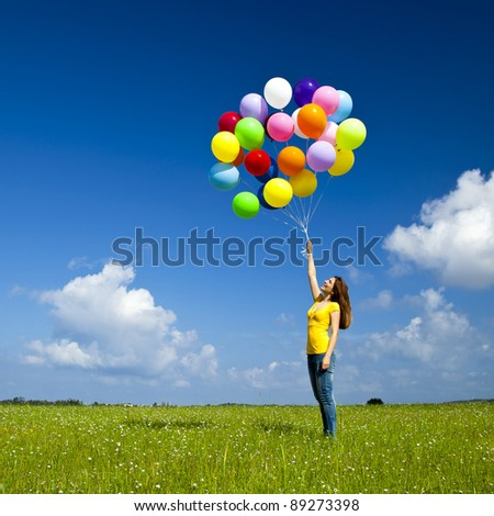 Happy young woman with colorful balloons on a green meadow