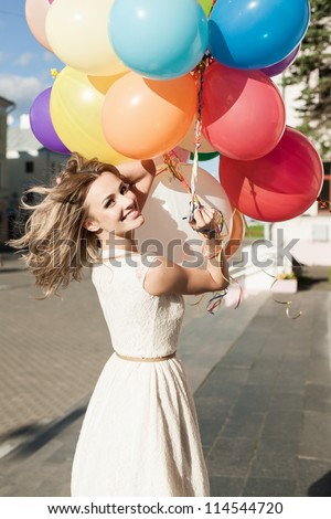 Happy young woman with colorful latex balloons keeping her dress, urban scene, outdoors