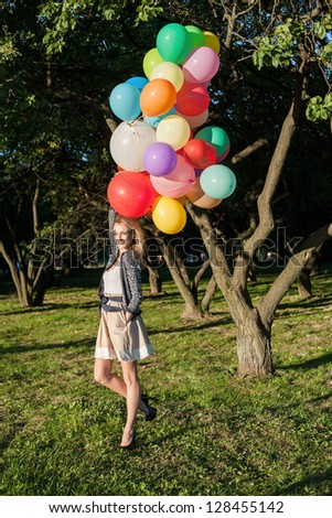 Happy young woman with colorful latex balloons, outdoors