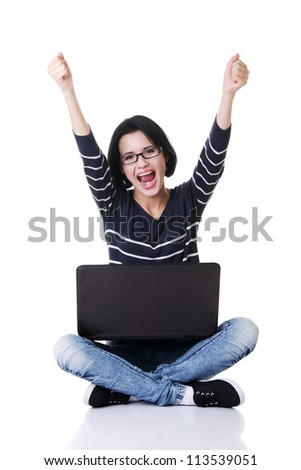 Happy young woman with fists up using her laptop, isolated on white.
