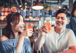 happy young woman with friend dining and drinking beer at restaurant