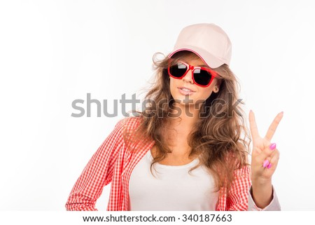 Happy young woman with glasses and hat showing two fingers - Shutterstock ID 340187663