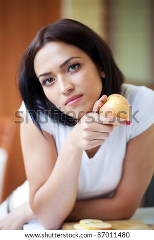 Happy young woman with green apple
