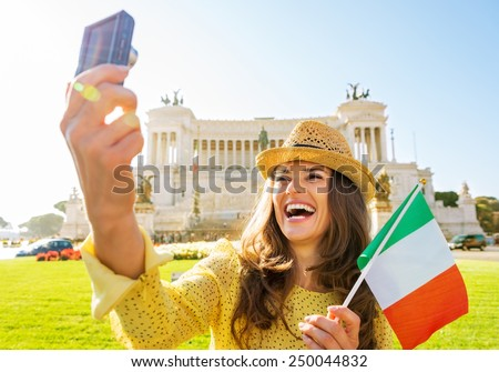 Happy young woman with italian flag making selfie on piazza venezia in rome, italy