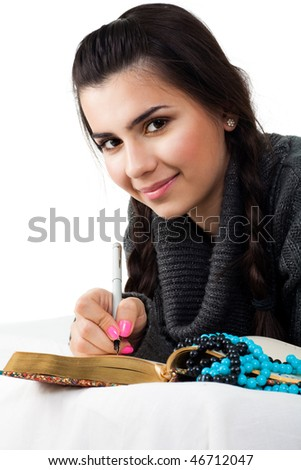 Happy young woman with mysterious smile write notes into notepad - stock photo