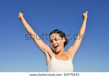 Happy young woman with raised arms against blue sky