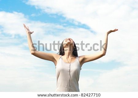 Happy young woman with raised arms and closed eyes against blue sky