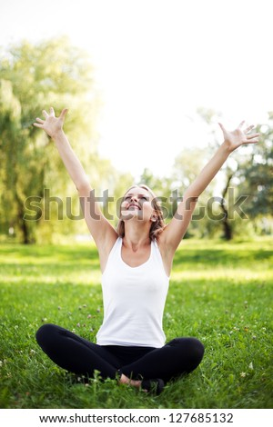 Happy young woman with raised arms sitting on grass