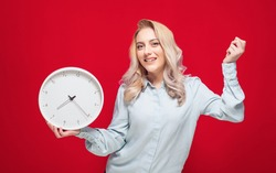 Happy young woman with smile face holding wall clock, isolated on red background. Exhilarated girl. Studio shot