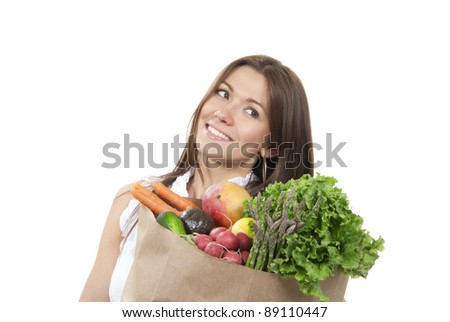 Happy young woman with supermarket shopping bag full of groceries, cucumbers, salad, asparagus, radish, avocado, lemon, mango, carrots on white background