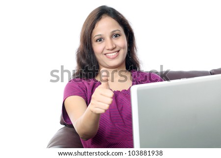 Happy young woman with thumb up sitting on the sofa and working on laptop