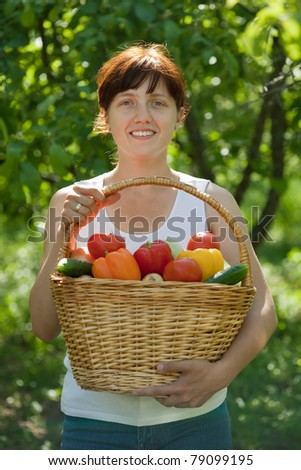 Happy young woman with vegetables harvest in garden