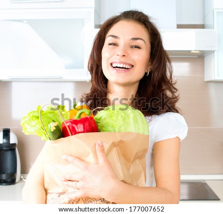 Happy Young Woman with vegetables in shopping bag. Beauty Girl in the kitchen Cooking healthy Food. Diet Concept. Young woman holding grocery shopping bag with vegetables. Healthy eating concept