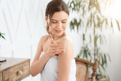Happy young woman wrapped in towel using body nourishing cream or lotion. Pretty lady using moisturizer for her smooth and silky skin after morning shower, rubbing her shoulder, copy space, sun flare