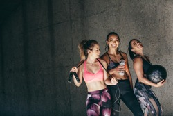 Happy young women standing together and smiling after exercising. Group of female friends relaxing after workout outdoors.