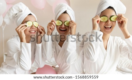 Photo of  Happy young women wear white bathrobes towels on head make cucumber facial skin care mask on eyes laughing relaxing together, smiling girls friends having fun on spa beauty salon party with balloons