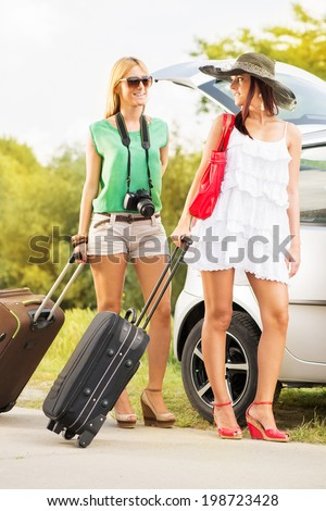 Happy young women with luggage standing by the car. They pack up their bags and going on holiday.