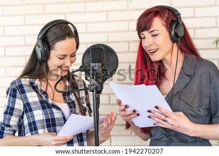 Happy young women with scripts smiling and resting near microphone during break in film dubbing session Stok fotoğraf ©