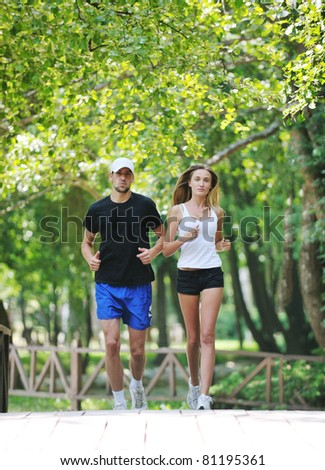 happy young younpe jogging and runing outdoor in nature at sunny day - stock photo