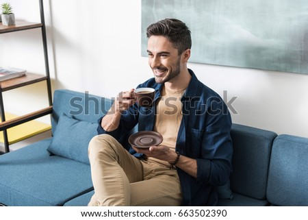 Happy youthful guy having leisure time in his apartment - Shutterstock ID 663502390
