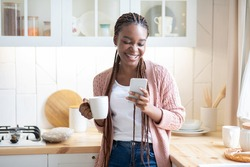 Hapy Black Lady Drinking Morning Coffee And Using Smartphone In Kitchen