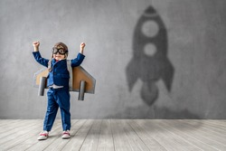 Hapy child wants to become a astronaut. Funny kid dreams of becoming a rocket pilot. Imagination and motivation concept