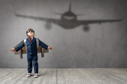 Hapy child wants to become a pilot. Funny kid dreams of becoming a aviator. Imagination and motivation concept