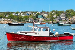 Harbor at Stonington, Maine, USA with a red lobster boat in the foreground