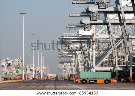 Harbor cranes and robot trucks with containers in a large port.