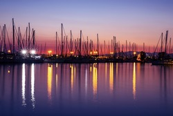 Harbor in the evening, silhouettes of luxury sailboat moored in the port, beautiful view on yachts with many glowing lights, active summer vacation