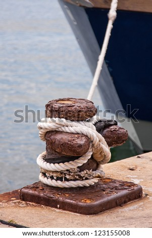 harbor quayside with rusted bollard rope and ship in background
