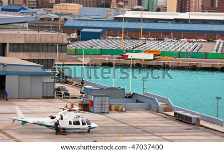 harbor with cars waiting to be uploaded for export, harbor pilot helicopter in foreground