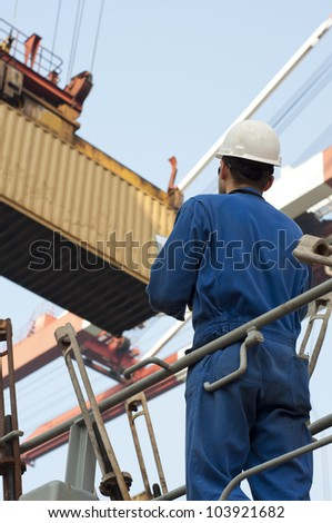 Harbor worker - watching the loading operation . Real situation photo.