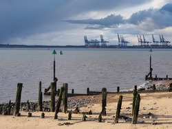 Harbour and Port of Felixstowe at dusk with remains of old wooden jetty, channel markers, groins, and cranes under dark clouds loading containers onto a cargo ship, Felixstowe, Suffolk, UK