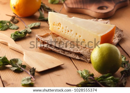 Hard cheese, lemon, lime and mint on a wooden background, wooden spatula, mint leaves with cheese and holes, rustic style, parchment cheese, healthy food, vegan