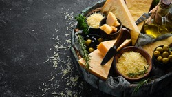 Hard cheese with olives and cheese knife on black stone background. Parmesan. Top view. Free space for your text.