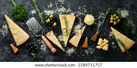 Hard cheese with olives and cheese knife on black stone background. Parmesan. Top view. Free space for your text. Foto d'archivio ©