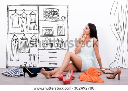 Hard choice. Thoughtful young woman in dress looking at the sketch on the wall while sitting on the floor with clothes and shoes laying around her