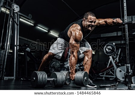 Hard Core Bodybuilding. Bodybuilder ready to lift heavy dumbbell