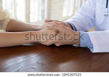 Hard diagnosis is not verdict. Close up of man doctor holding woman customer hands with care compassion support, confident qualified medical specialist convincing encouraging patient to take treatment