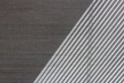 Hard diagonal shadows on grey textured wall from a window roller shutter or blinds. Attractive abstract half frame composition