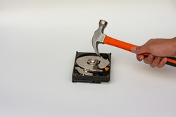 Hard disk drive platter being destroyed with a hammer on a white background.