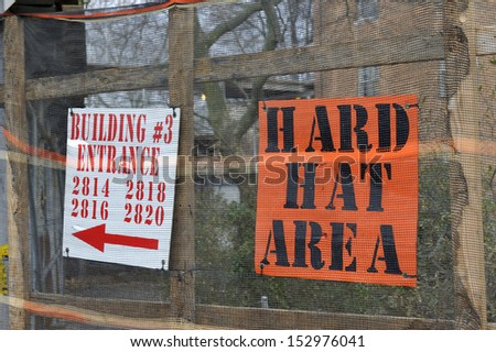 Hard hat area sign post on a fence outside a construction zone.